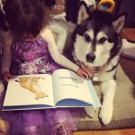 Ryan Leigh Dostie's Daughter reading a book with pet dog